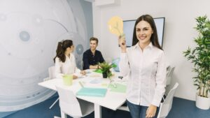 portrait-smiling-young-businesswoman-with-light-bulb-icon-standing-office-min