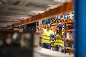 warehouse-workers-checking-inventory-large-distribution-warehouse-storage-min