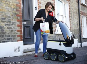 woman receive grocery from robot starship