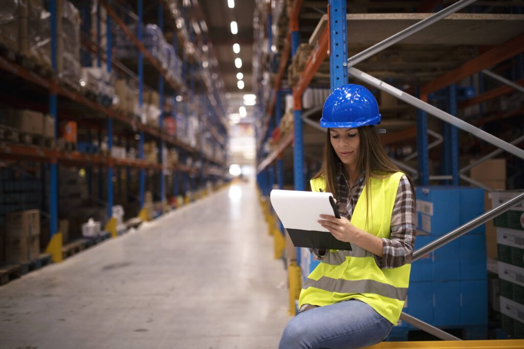 industrial-worker-checking-goods-inventory-large-warehouse-storage-center-writing-report-distribution-results-min