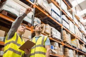 two men in warehouse pointing at inventory